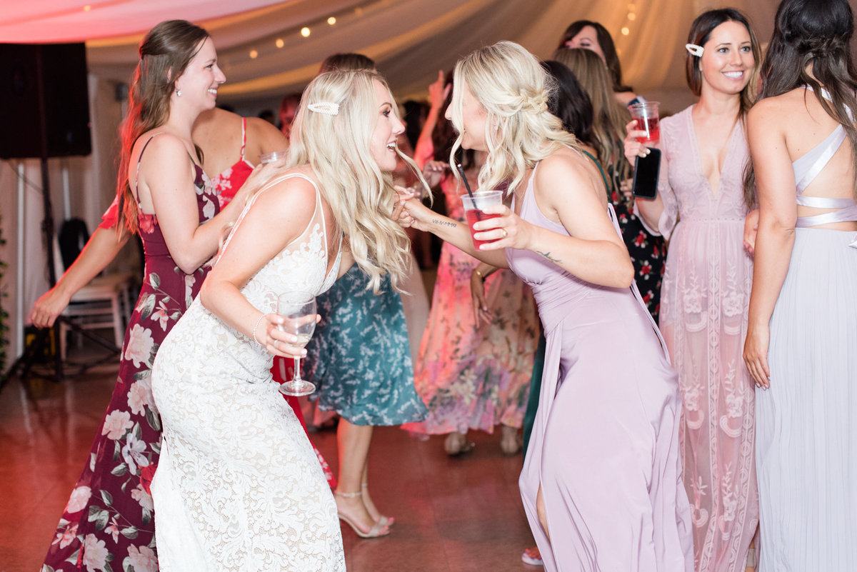 Bride dancing with bridesmaid during her wedding at Stepstone Centre in Thunder Bay