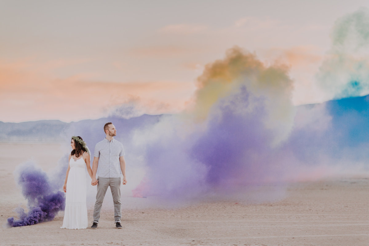 Lake Tahoe wedding photos a bride and groom pose in the desert in front of colorful smoke