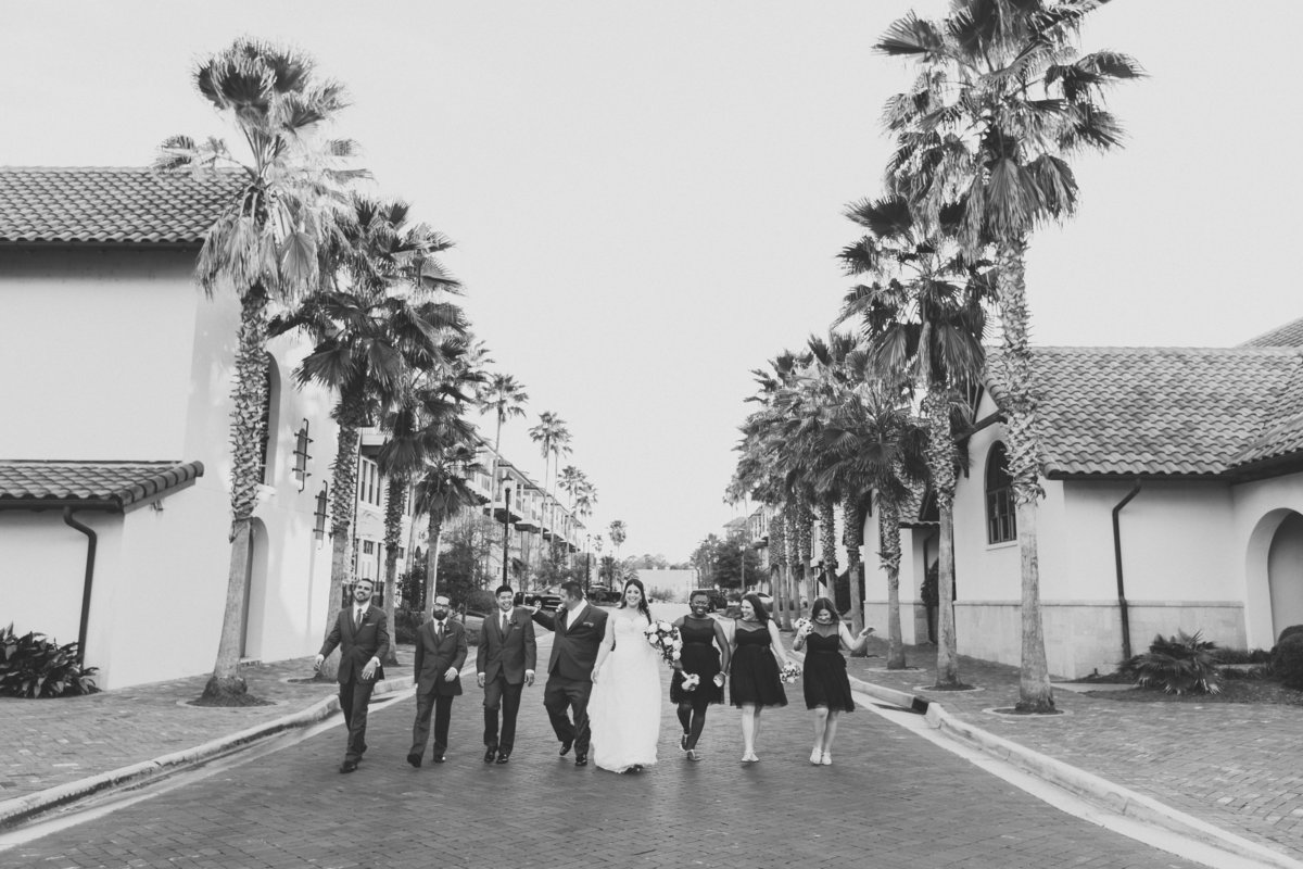 Bridal party walking down the street laughing