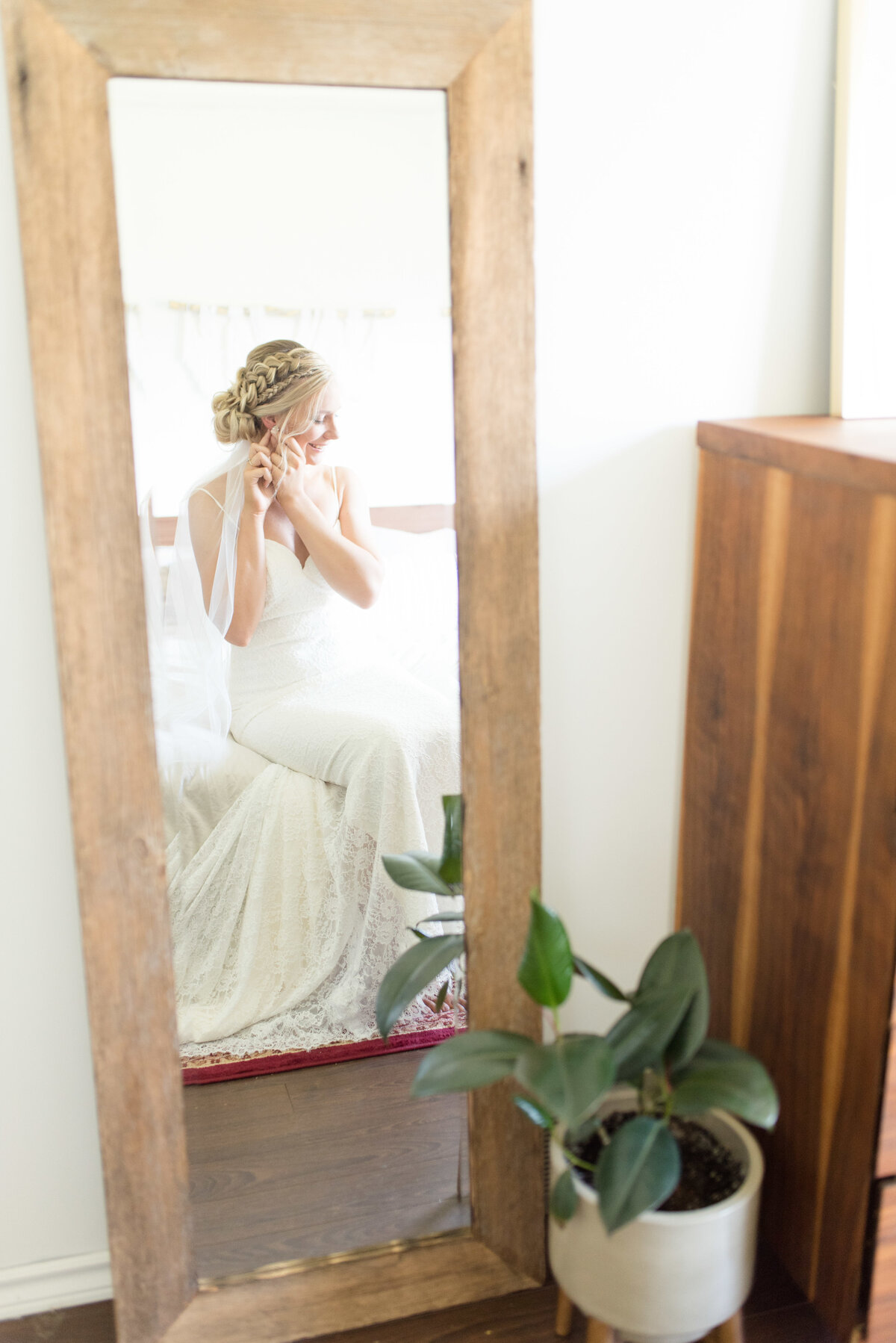 A bride sits on her bed in front of a handmade mirror to put on her earrings