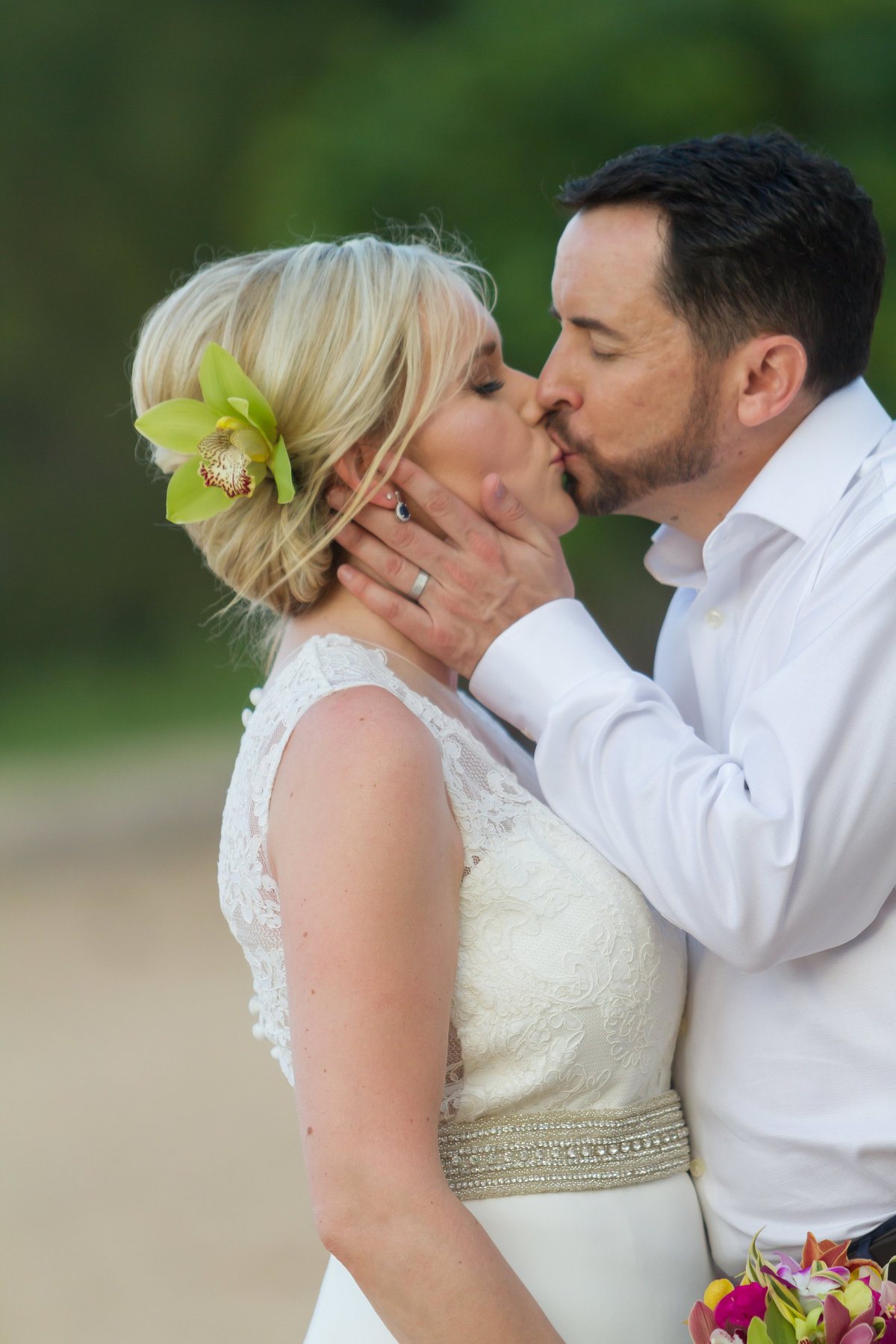 Bride with orchid in her hair and groom kissing.