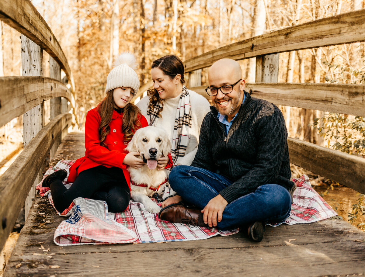 Family with dog on wooden bridge