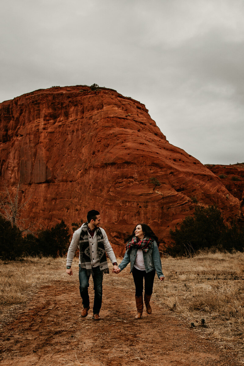 engaged couple walking in front of a red rock mountain