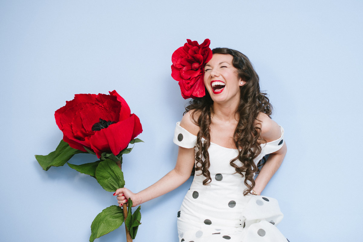 Alternative bride with single large red paper flower on a blue wall