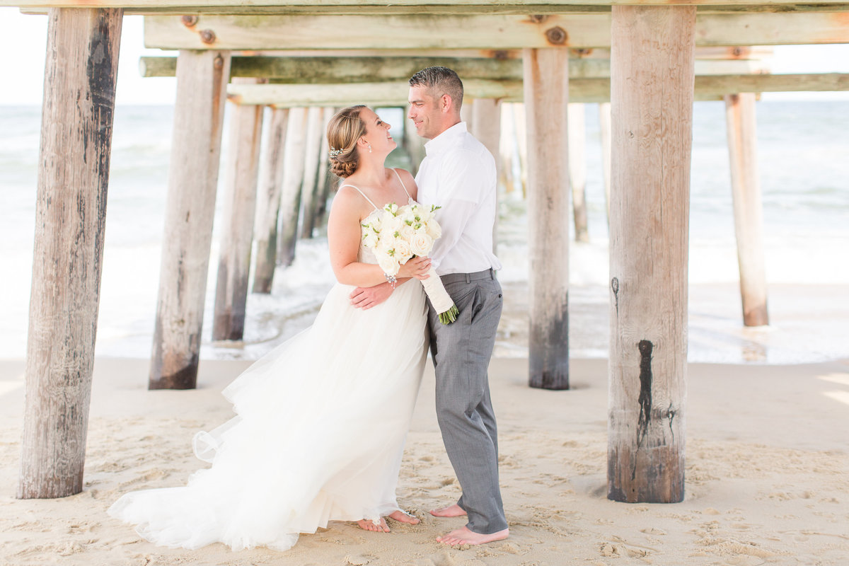 bride and groom posing under the Sandbridge Beach Pier