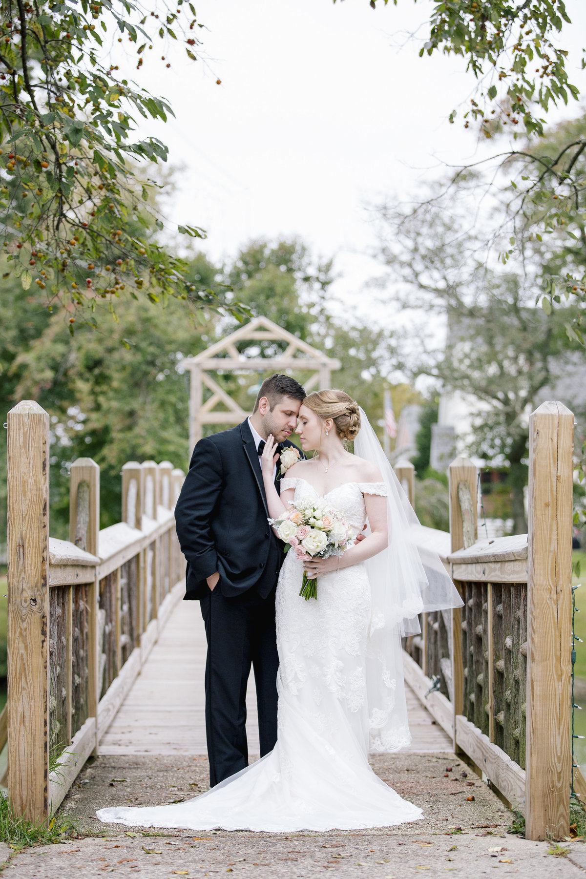 bride and groom on bridge at spring lake park wedding