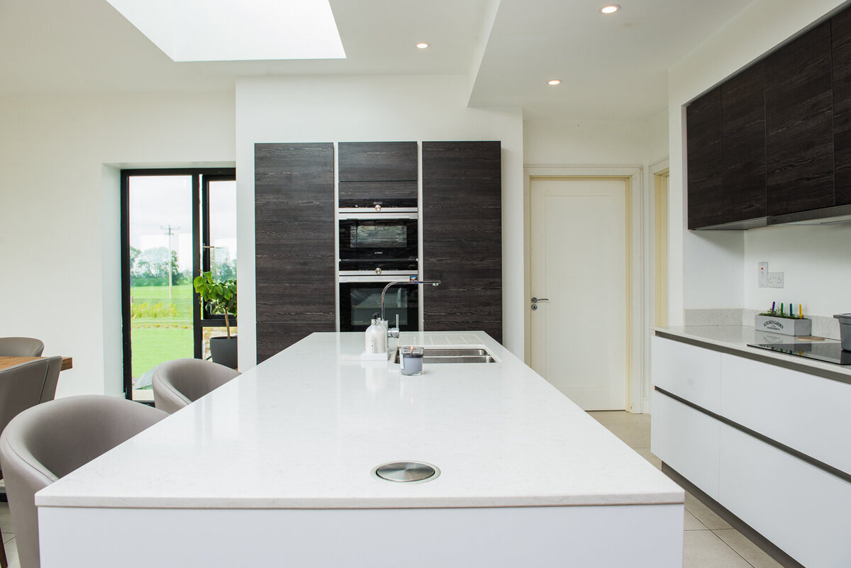 Modern kitchen with black and  white units and quartz island