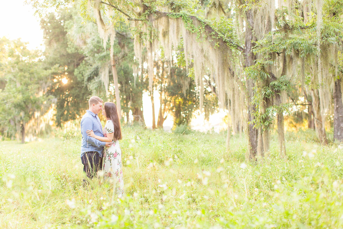 Engaged couple hugging underneath the oak trees
