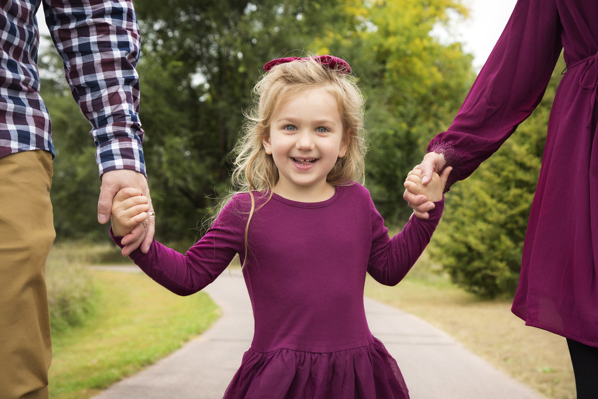 sioux falls family photography girl holding mom and dad hands sioux rec area south dakota
