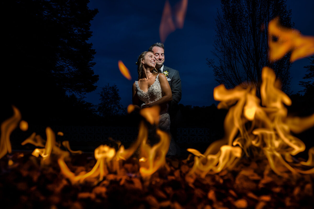 Bride and groom stand in front a  fire pit with a dark blue sky in the background