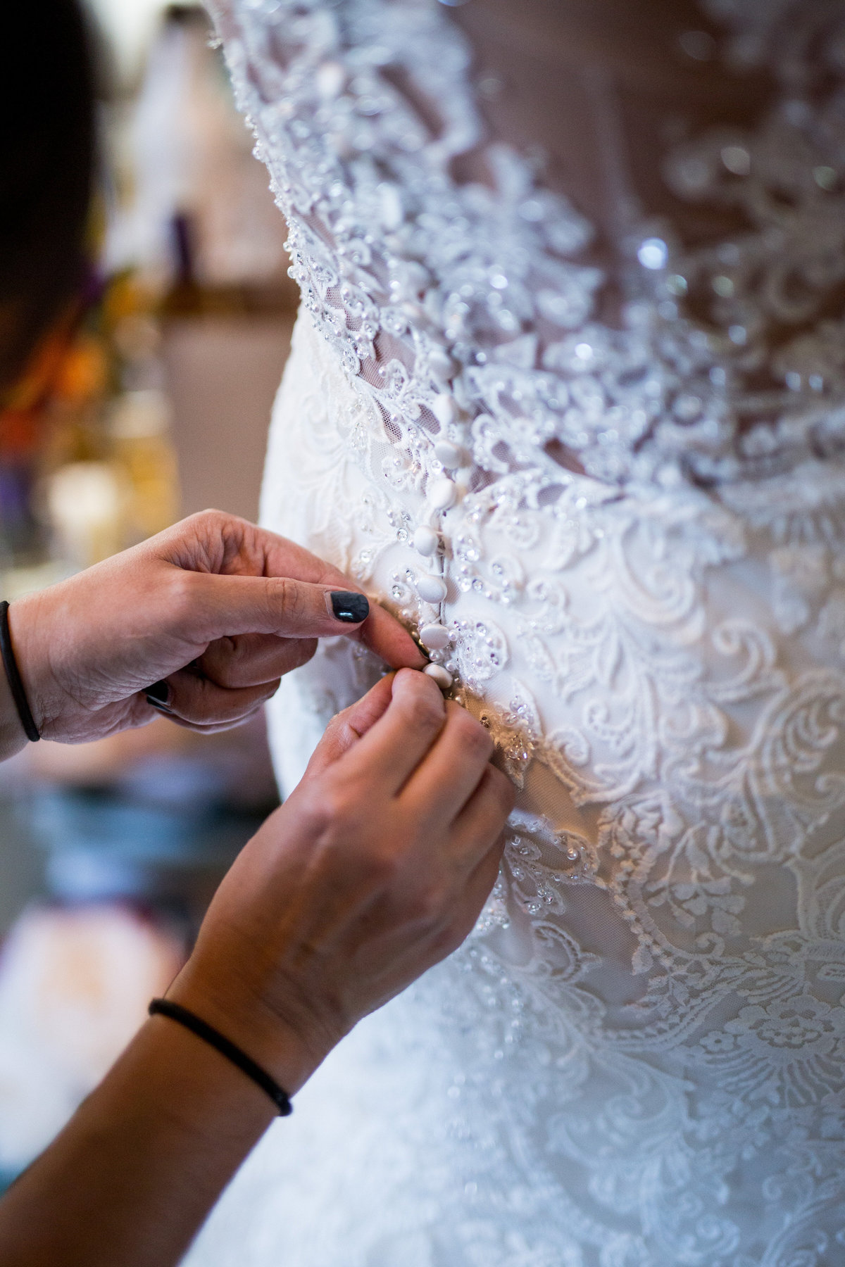 mother of bride buttoning bridal gown of bride during getting ready in san antonio wedding