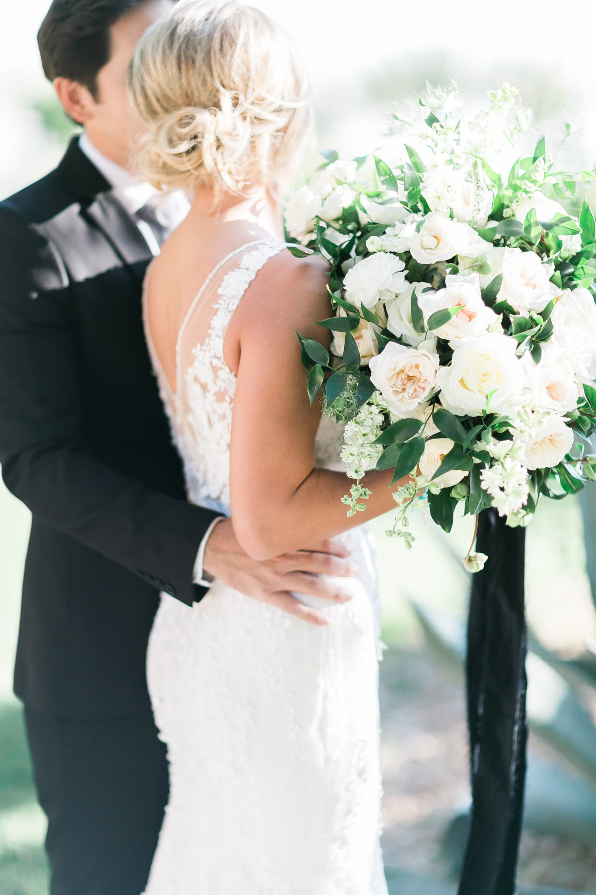 bride and groom photo at Red Rock Country Club with white floral bouquet and black velvet ribbon
