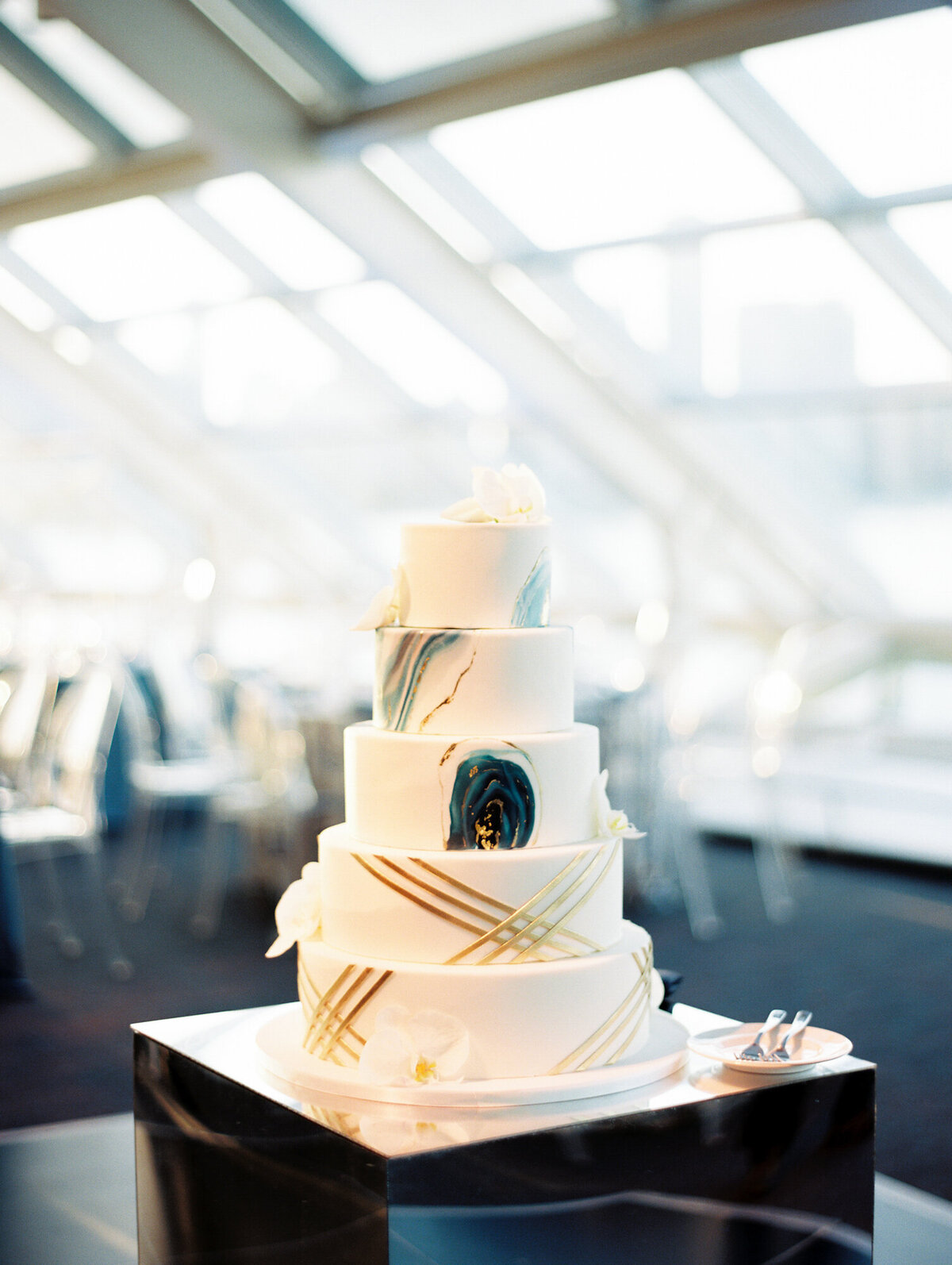 Five tier marble wedding cake on mirrored stand