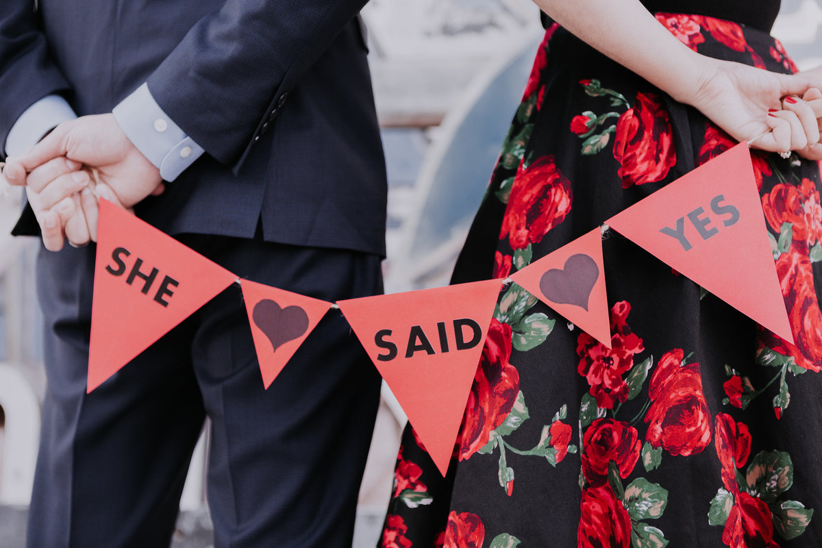 Lake Tahoe engagement pictures couple holds a sign that says she said yes