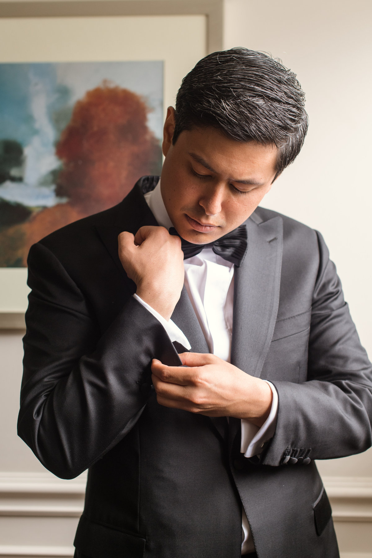 wedding photo of groom adjusting cufflinks at The Garden City Hotel