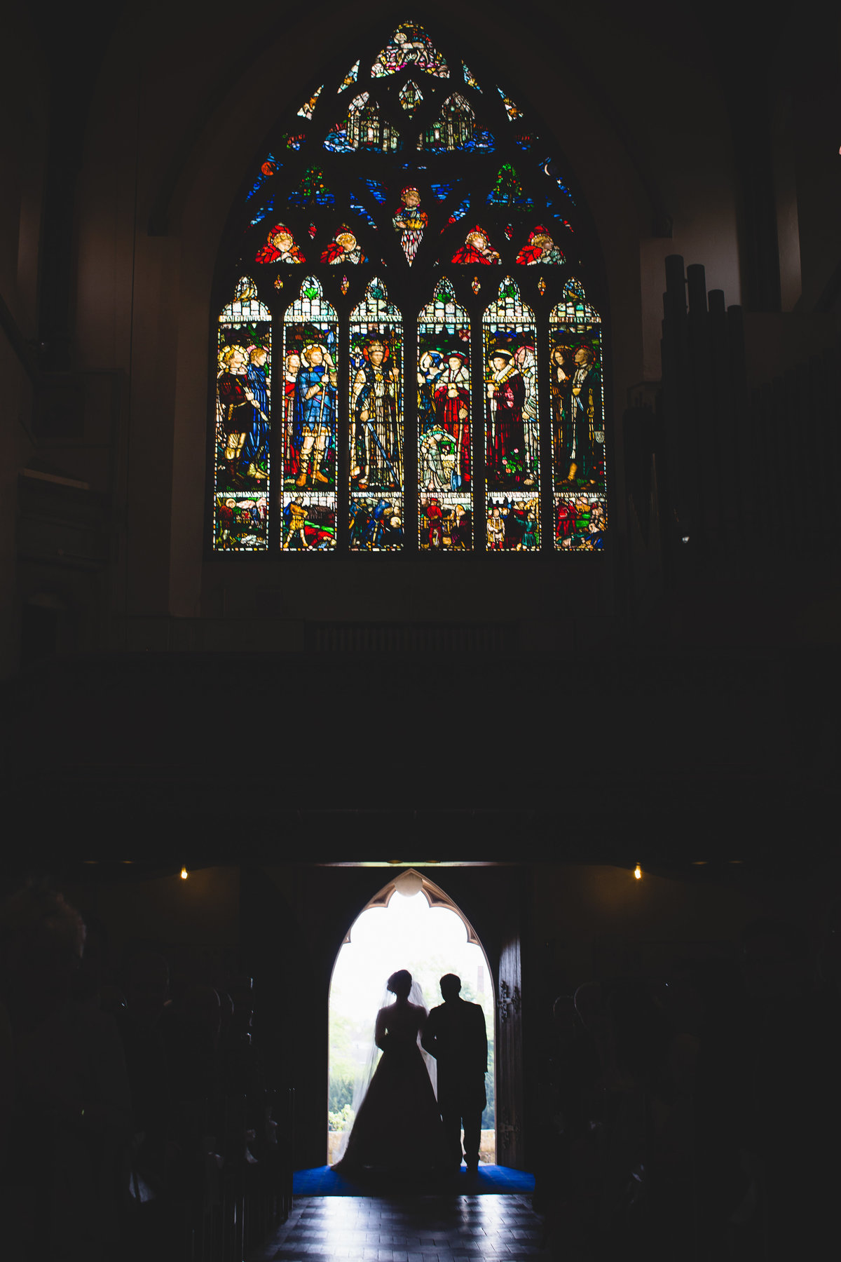 bride entering the church silhouette in front of stained glass window