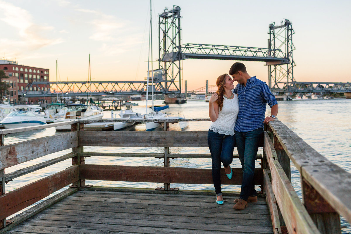 The Memorial Bridge in Portsmouth NH sits behind the couple out on the docks