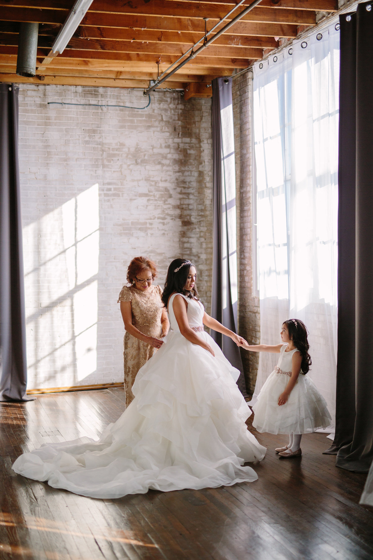 Bride holding flower girls hand while mother of bride buttons gown in downtown San Antonio wedding