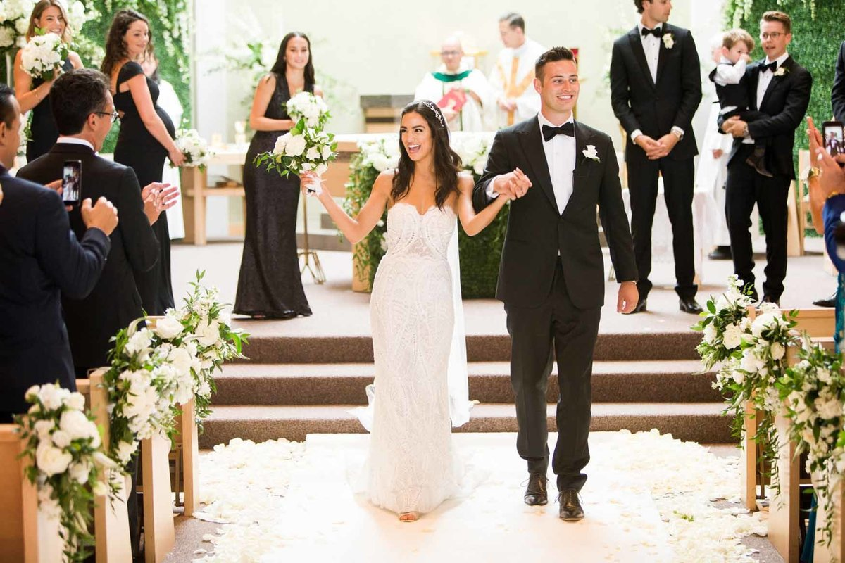 Bride and Groom walking down aisle with white rose petals