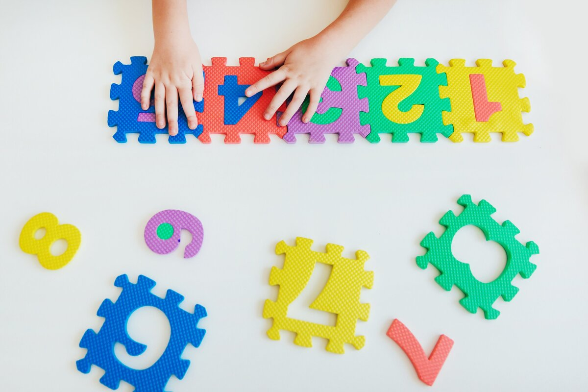 childs-hands-playing-with-numbers-learning-simple-multiplication-colorful-bright-puzzle-numbers-on_t20_XxrkZz