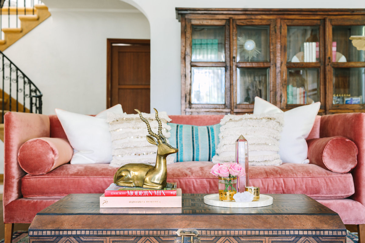 Rustic and feminine living room  with pink velvet sofa and Moroccan wood coffee table