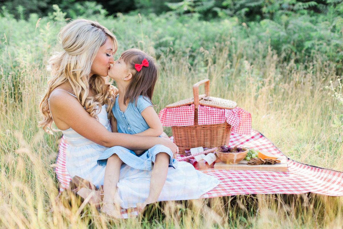 mother and daughter kissing while having a picnic