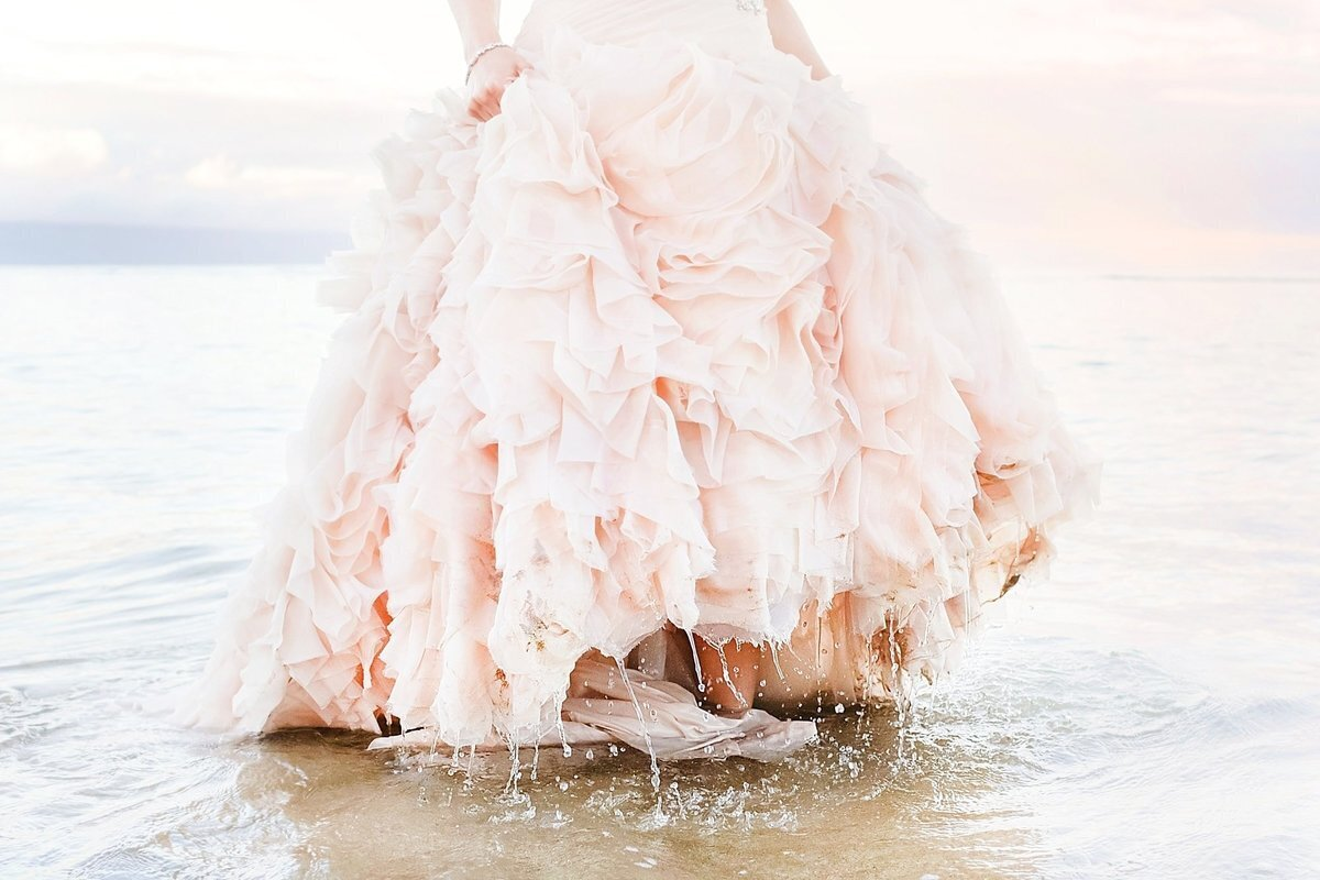 Bride in pink fluffy wedding gown holds her train as it drips with saltwater after her trash the dress session on Maui