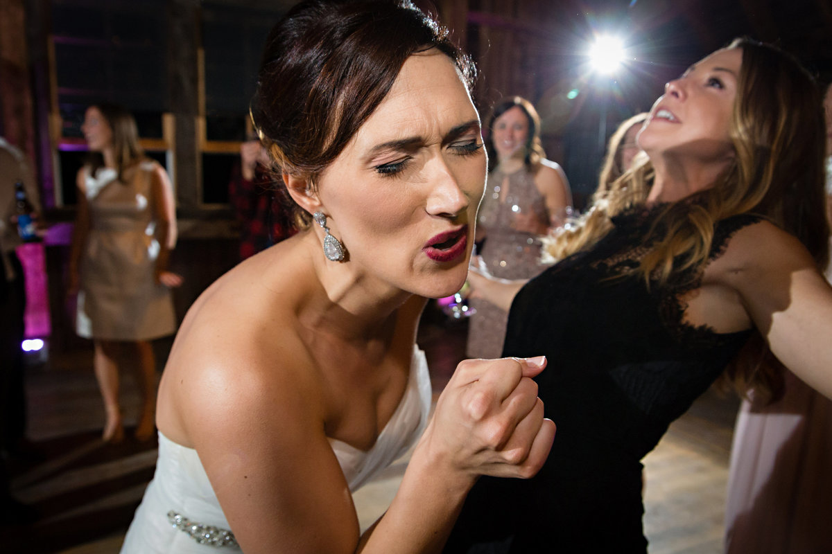 The bride sings along to a rap song at her wedding reception at Skinner Barn in Vermont