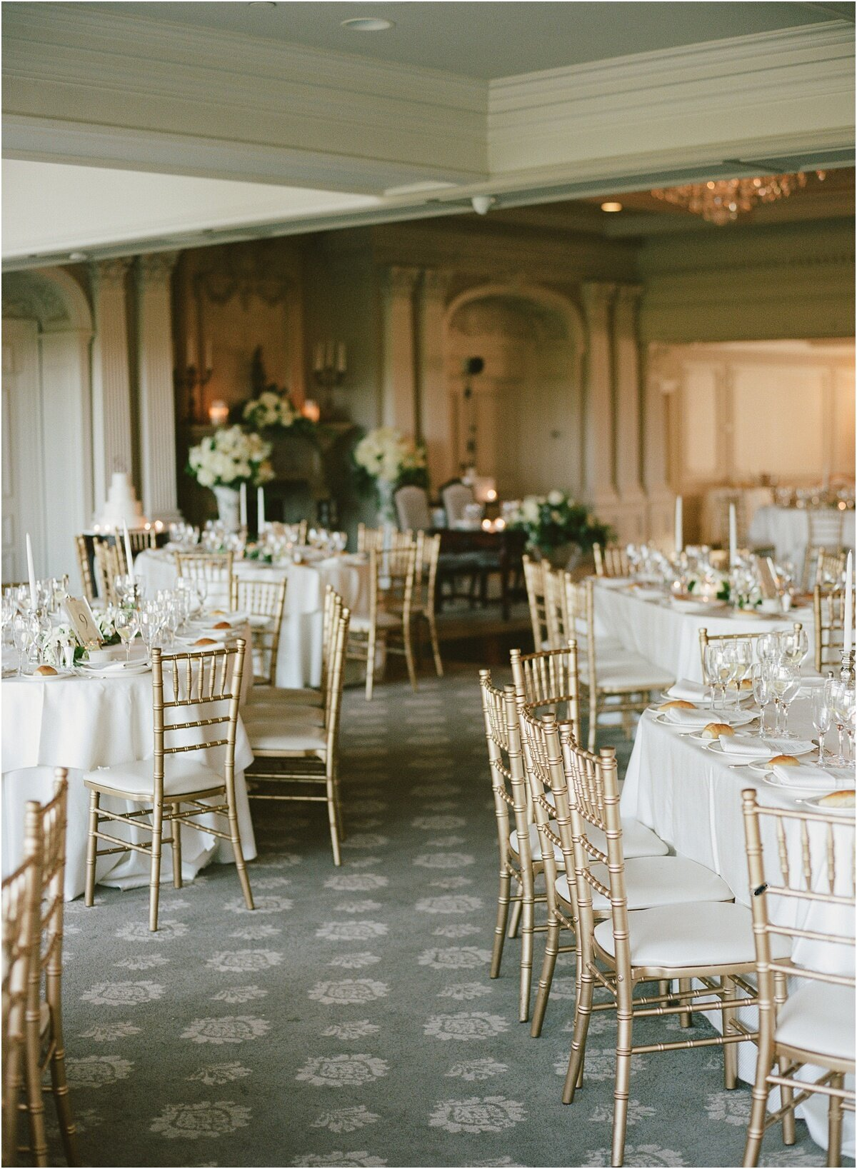 film image of reception room gold chairs white linens ballroom