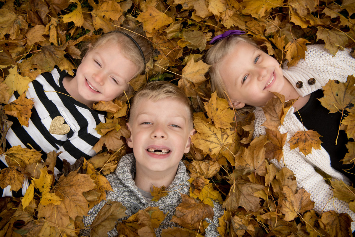 kids in fallen leaves on a crisp autumn day.