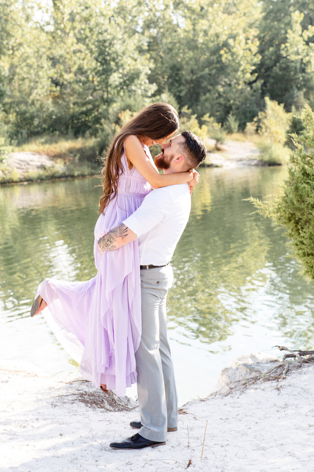 Summer Sunset Romantic Engagement Session in lavender maxi dress guy lifting girl on white sand by water at Klondike Park in St. Louis by Amy Britton Photography Photographer in St. Louis
