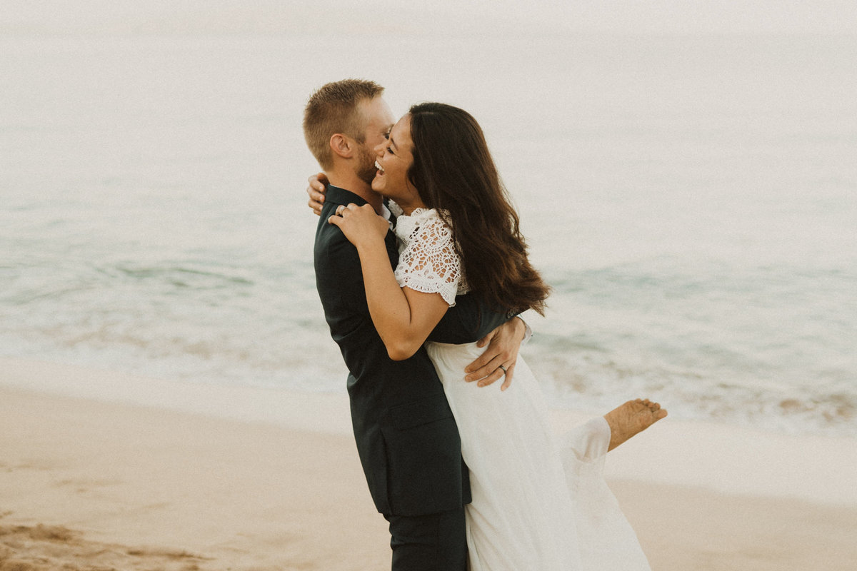 bride & groom laughing on beach