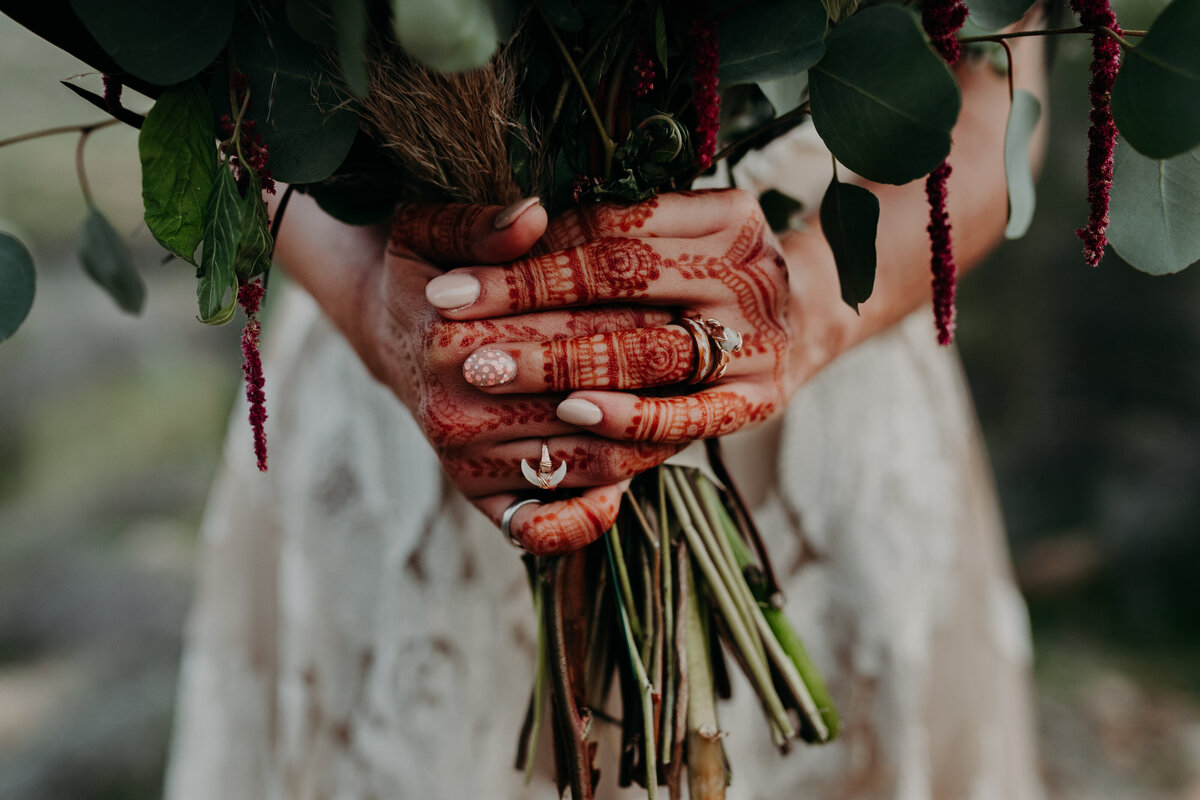 Bride with Henna covering her hands holds bouquet and shows off her rings