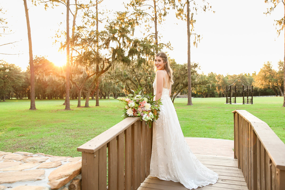 Beautiful bride poses at wedding venue with at golden hour with sunset in the background on a bridge with her wedding bouquet