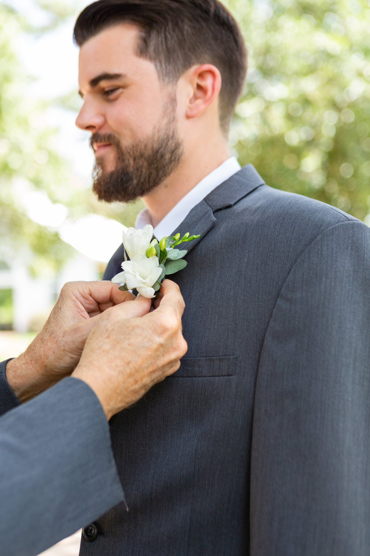 Dad Pinning Boutonnière on Groom