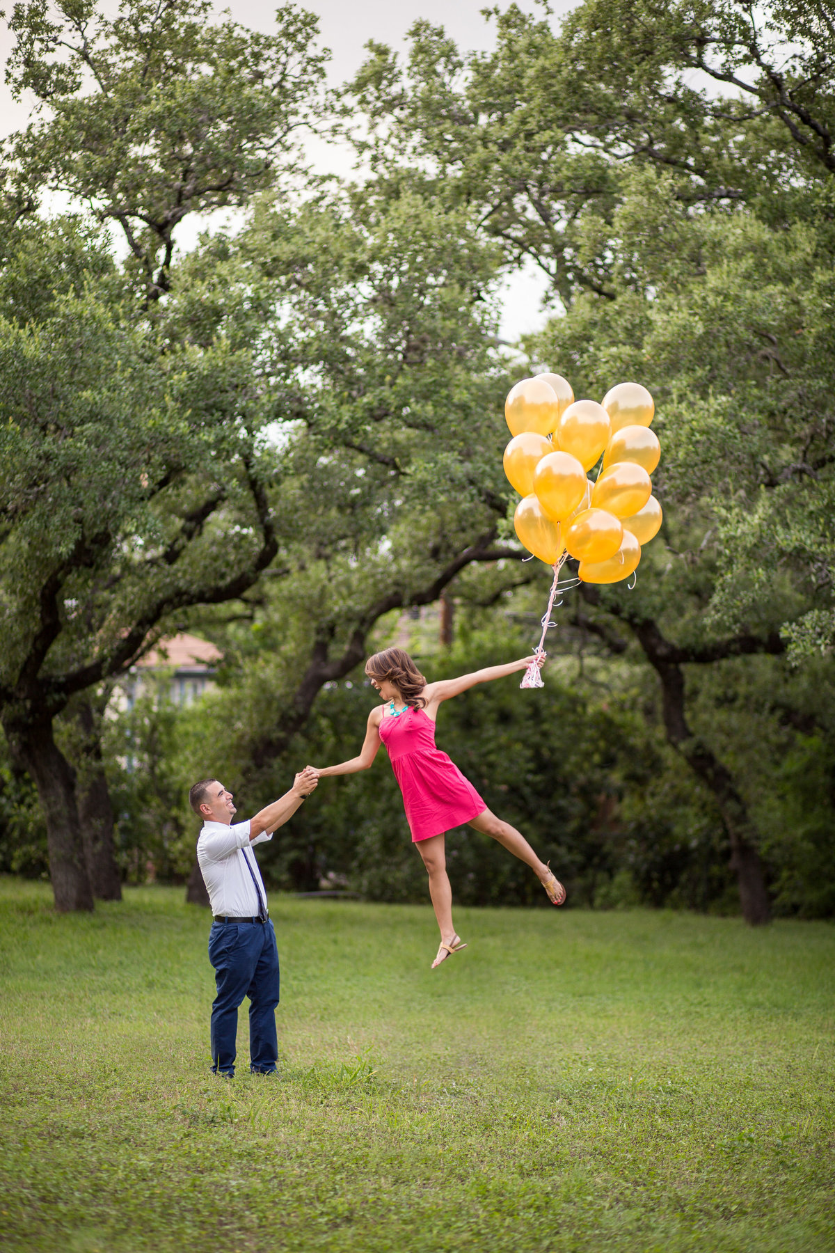 Engaged Woman holding her fiancé hand while she floats away holding balloons