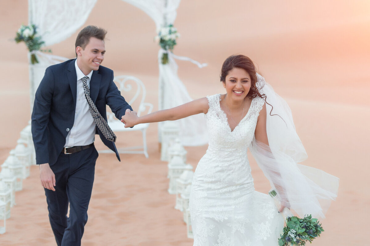 Wedding couple having fun during desert elopement shoot in Dubai organized by Lovely & Planned