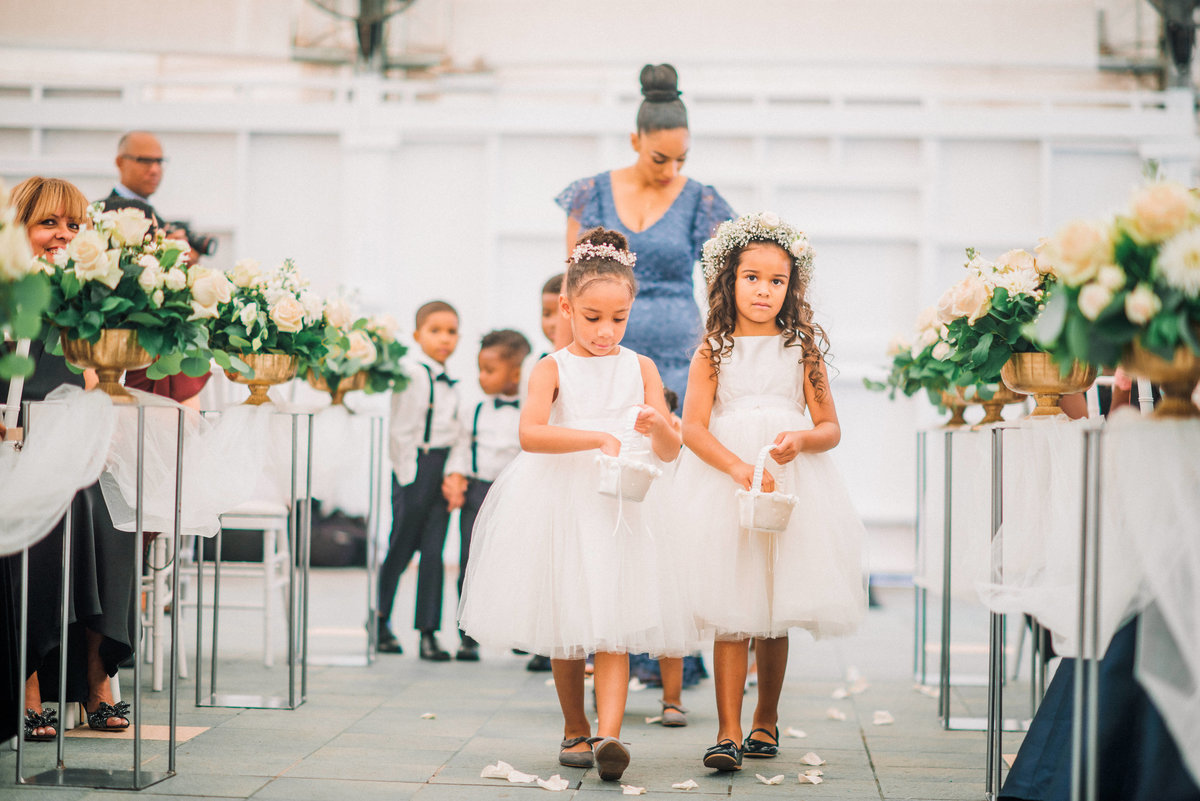 two young flower girls walking down the aisle