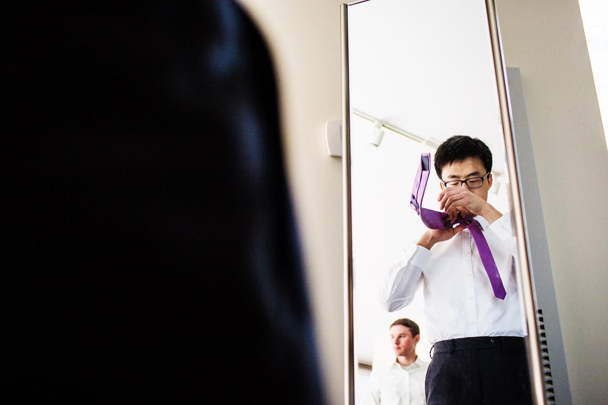A groom adjusts his tie before his Greenhouse loft wedding in Chicago.