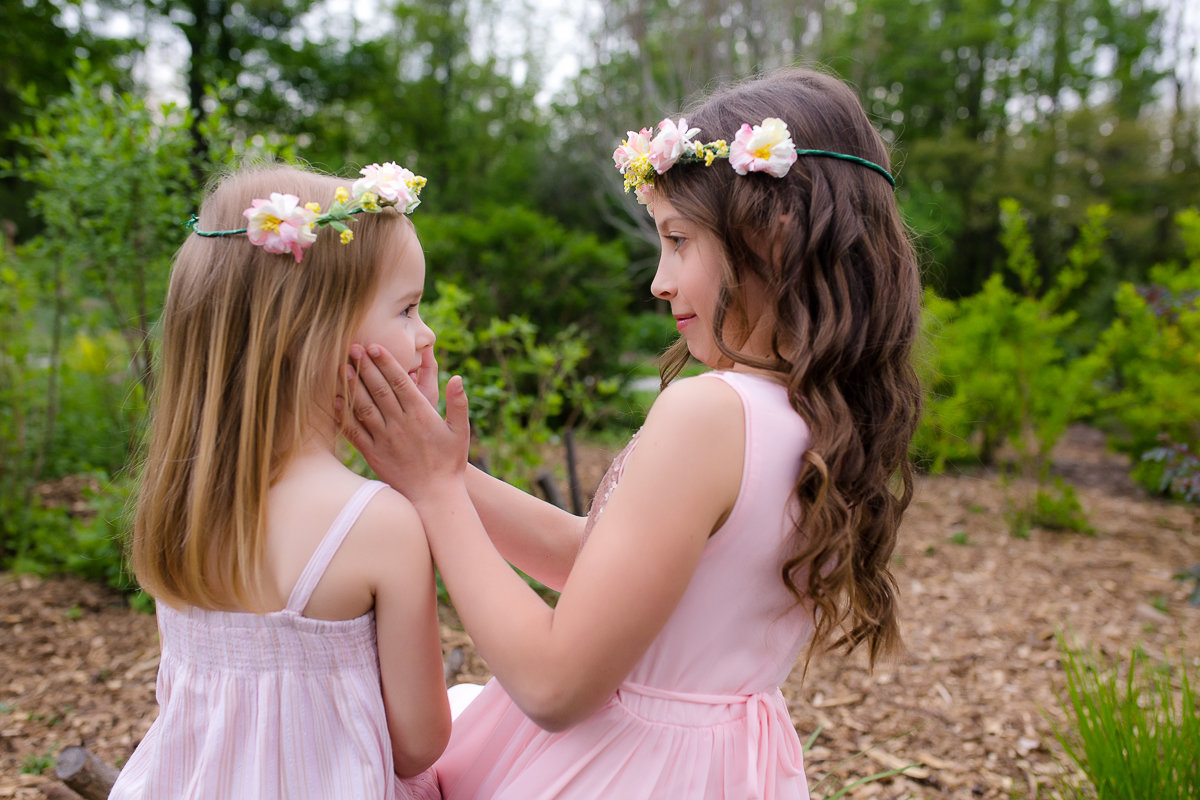 Older sister hugging younger sister outdoors {Burlington Child Photographer}