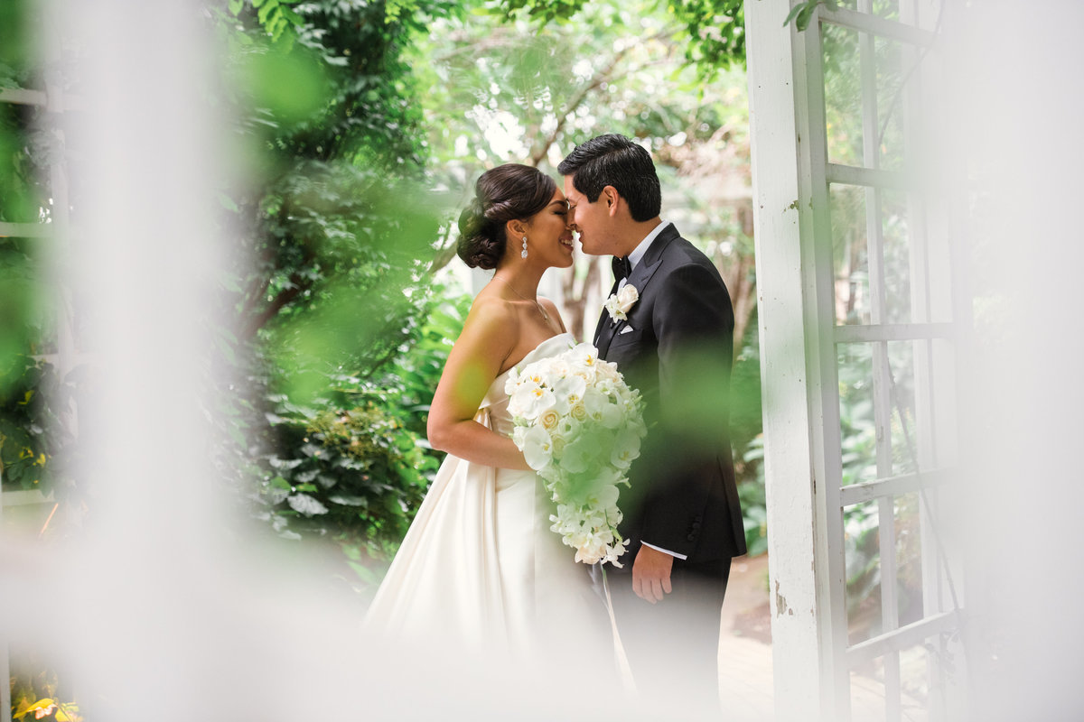 photo of bride and groom eskimo kiss outdoors from wedding reception at The Garden City Hotel