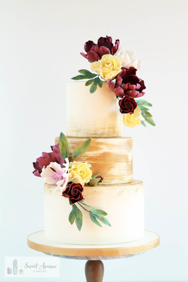 romantic floral wedding cake with brushed gold tiers