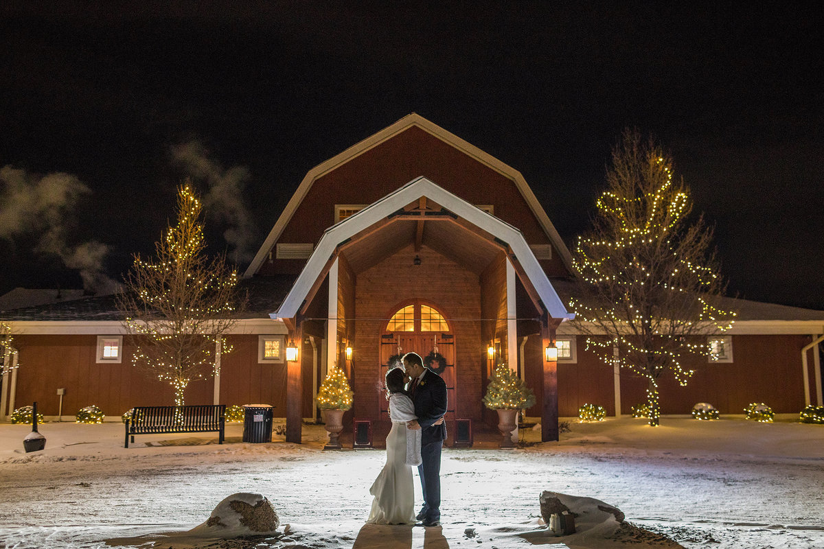 bride and groom kissing at night during a winter wedding