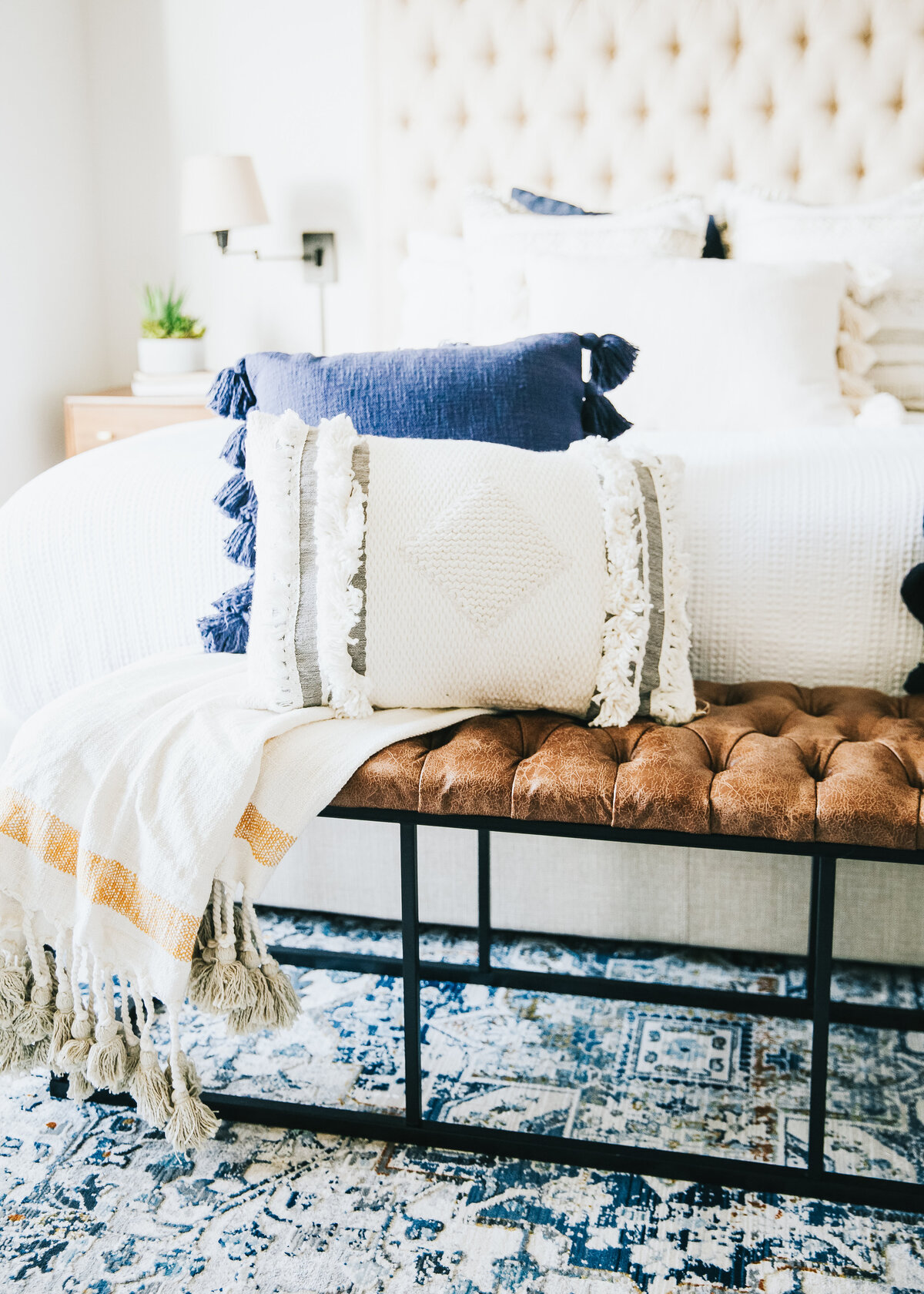 A white painted bedroom features a padded headboard white sheets, with a navy throw and a tan leather bench at the end.