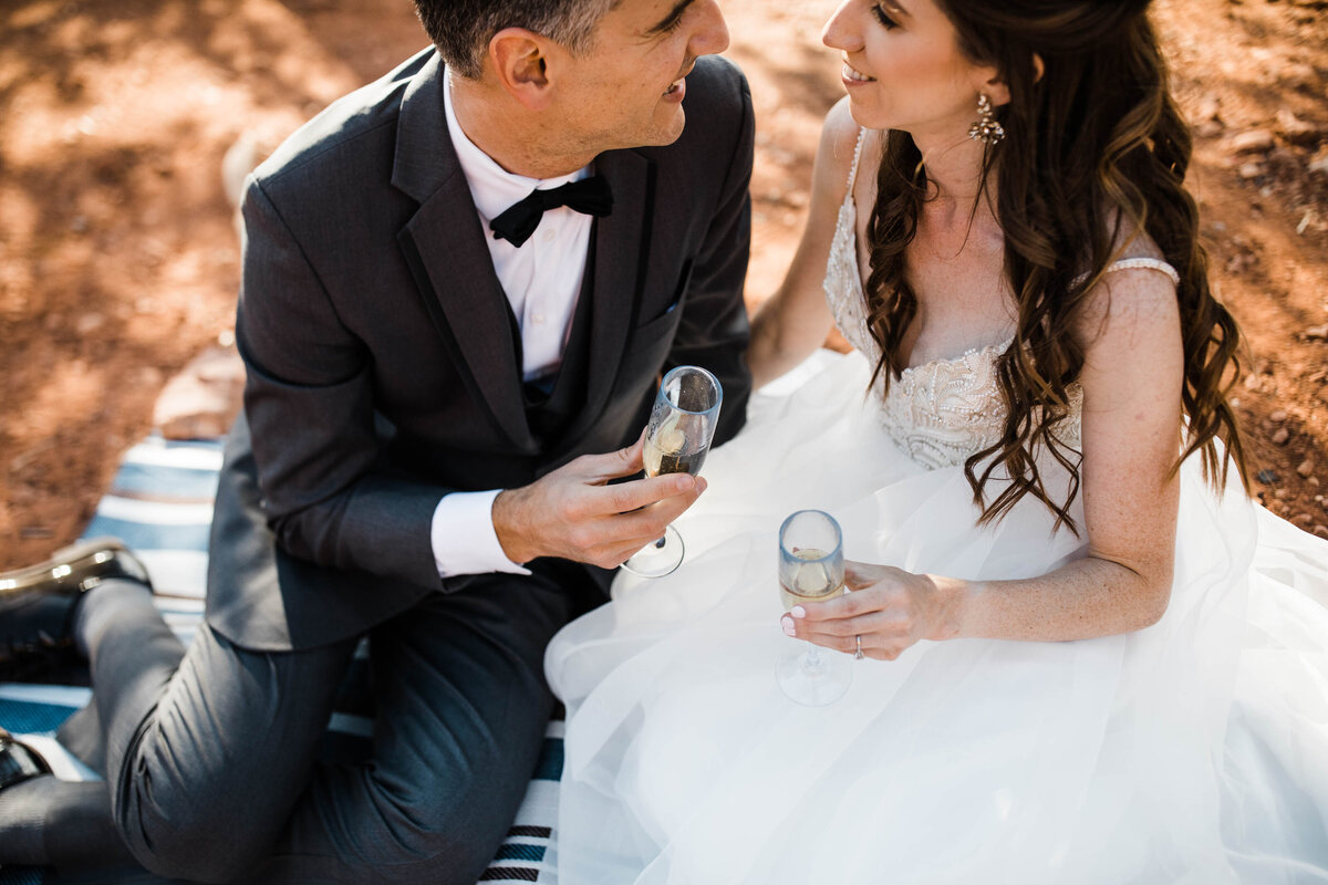 during their joshua tree elopement ceremony the bride looks up at her groom, smiling