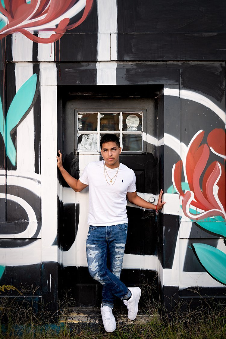 High school senior boy in white Polo tee and ripped jeans standing in doorway of painted black and white building with red roses