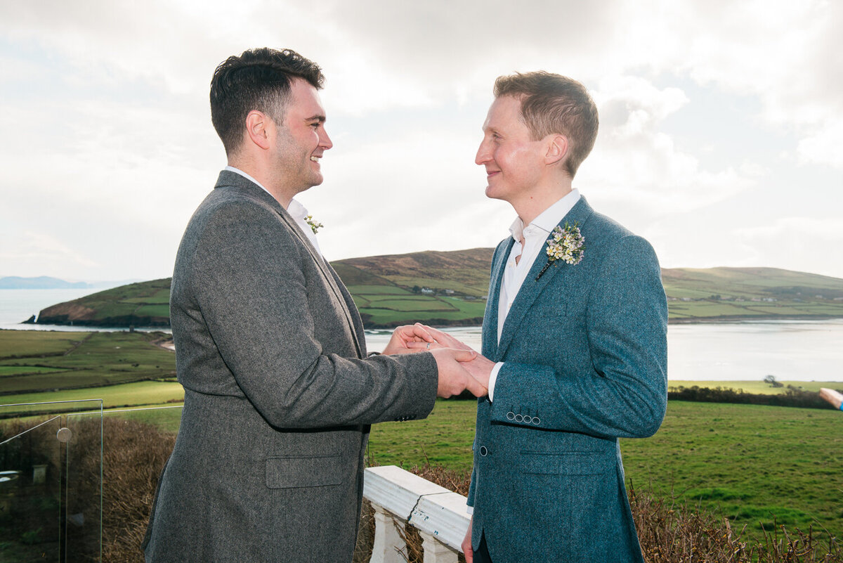 Gay grooms exchanging rings on the terrace of Pax House in Dingle