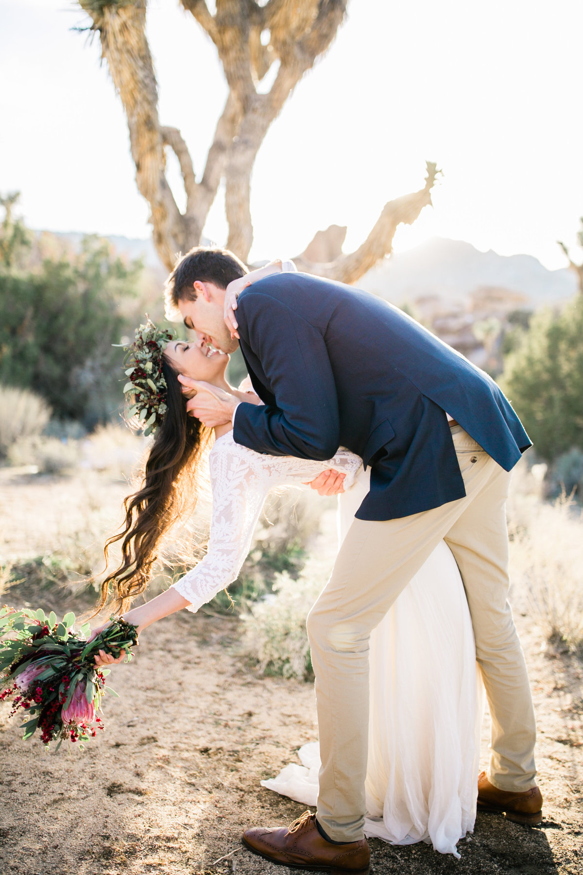 the groom dips his bride into a kiss in front of a joshua tree during their elopement