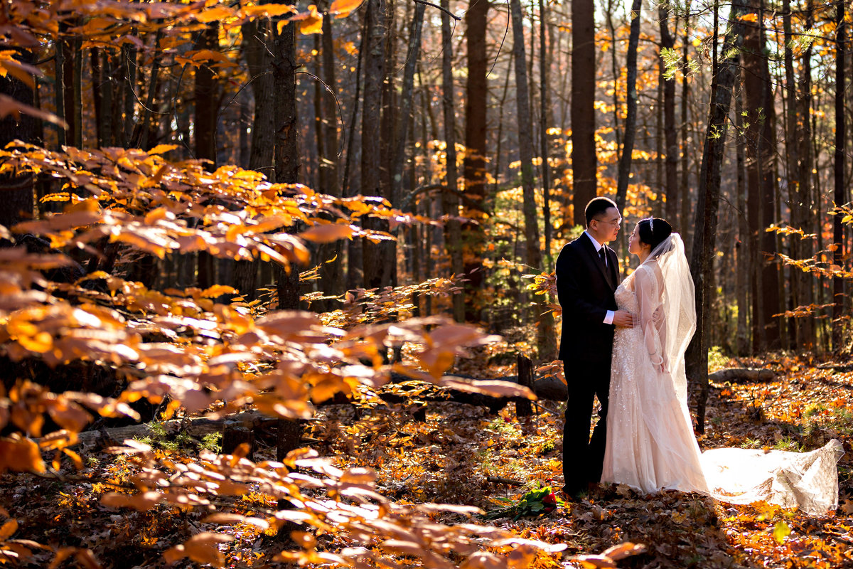 The elopement newlyweds hold each other close in the fall leaves at the Little Harbor Chapel in New Hampshire