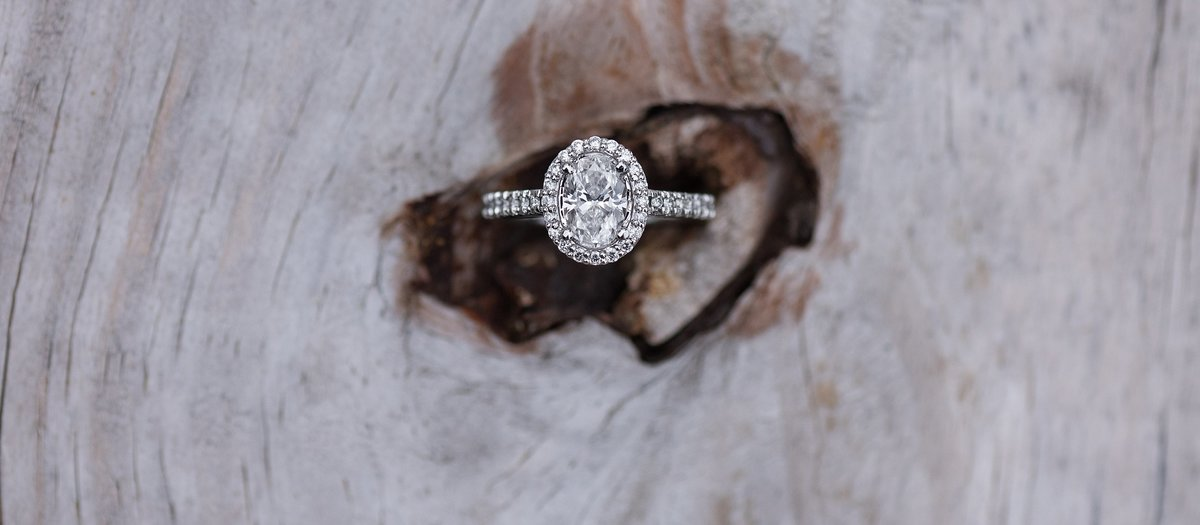 Oval cut diamond ring with halo in wood knot photo